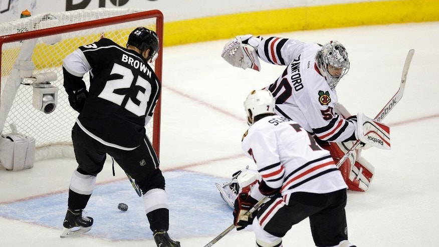 Los Angeles Kings' Dustin Brown, left, scores against Chicago Blackhawks goalie Corey Crawford, right, as Blackhawks' Brent Seabrook skates near during the first period of Game 4 of the Western Conference finals of the NHL hockey Stanley Cup playoffs on Monday, May 26, 2014, in Los Angeles. (AP Photo/Jae C. Hong)
