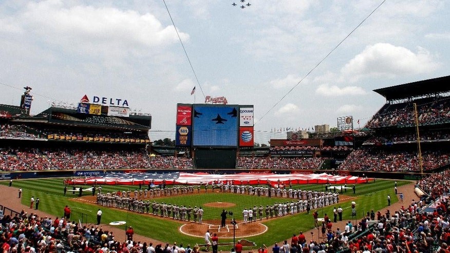 Jets fly over as members of the U.S. Military hold the American Flag across the outfield, in honor of Memorial Day, before a baseball game between the Atlanta Braves and the Boston Red Sox on Monday, May 26, 2014, in Atlanta, Ga. (AP Photo/Butch Dill)