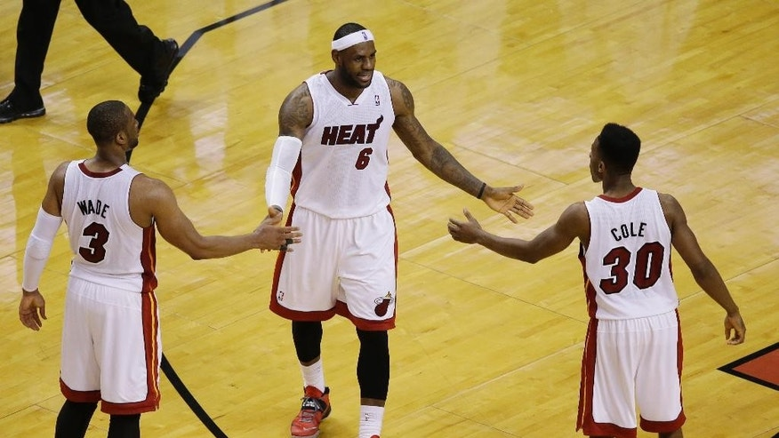 Miami Heat forward LeBron James (6) congratulates guards Norris Cole (30) and Dwyane Wade (3) during the second half of Game 4 in the NBA basketball Eastern Conference finals playoff series, Monday, May 26, 2014, in Miami. The Heat defeated the Pacers 102-90. (AP Photo/Lynne Sladky)