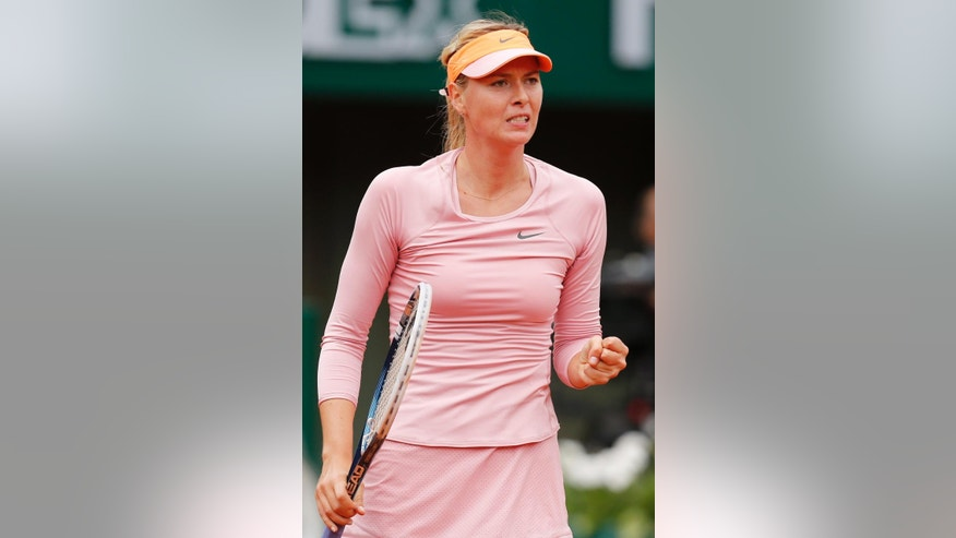 Russia's Maria Sharapova clenches her fist as she plays Bulgaria's Tsvetana Pironkova during the second round match of  the French Open tennis tournament at the Roland Garros stadium, in Paris, France, Wednesday, May 28, 2014. (AP Photo/David Vincent)