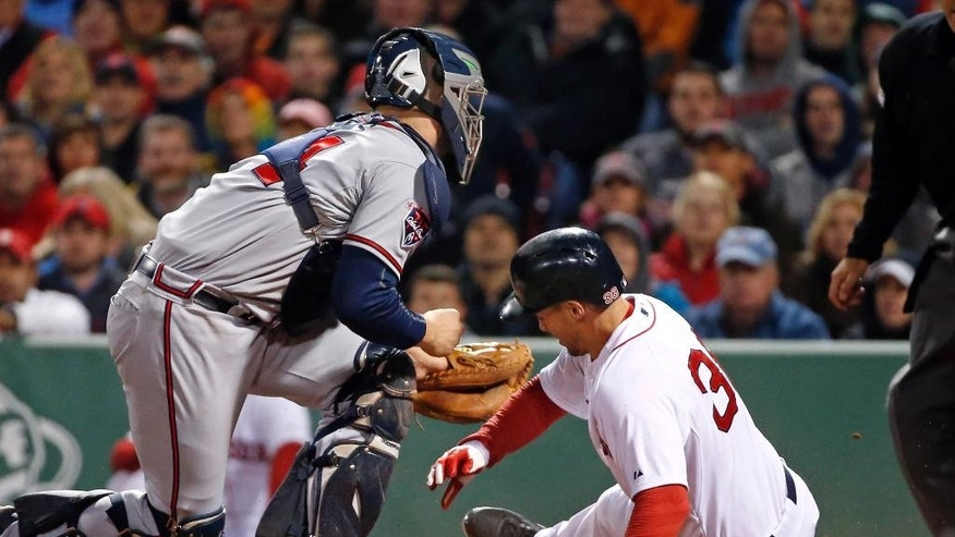 Atlanta Braves catcher Evan Gattis puts the tag on Boston Red Sox's Grady Sizemore, right, who is out trying to score on a fielder's choice in the sixth inning of a baseball game at Fenway Park in Boston, Wednesday, May 28, 2014. (AP Photo/Elise Amendola)