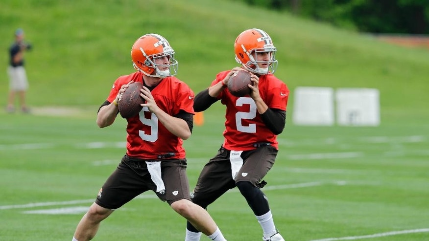 Cleveland Browns quarterbacks Johnny Manziel (2) and Connor Shaw (9) drop to pass during organized team activities at the NFL football team's facility in Berea, Ohio Wednesday, May 28, 2014. (AP Photo/Mark Duncan)