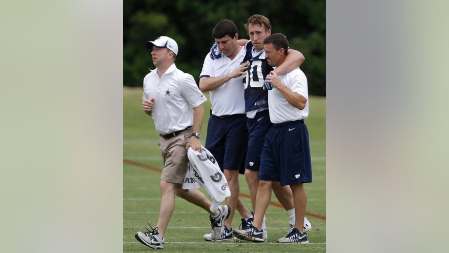 Dallas Cowboys linebacker Sean Lee is helped off the field by head athletic trainer Jim Maurer, left rear, and associate athletic trainer Britt Brown, right, after suffering an unknown left knee injury during an NFL football organized team activity, Tuesday, May 27, 2014, in Irving, Texas. (AP Photo/Tony Gutierrez)