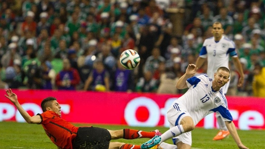 Mexico's Oribe Peralta, left, fights for the ball with Israel's Ben Sahar during a friendly soccer match in Mexico City, Wednesday, May 28, 2014. (AP Photo/Christian Palma)