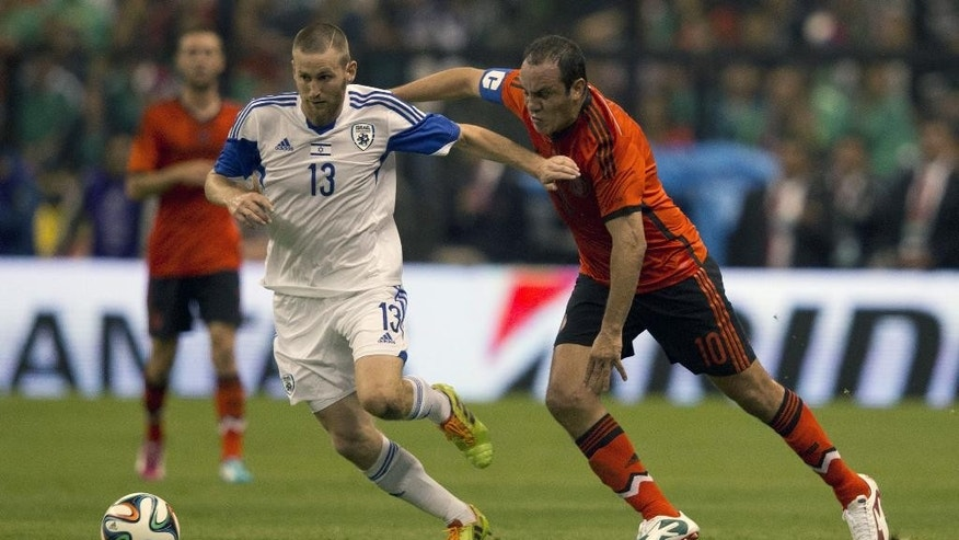 Israel's Sheran Yeini, left,  battles for the ball with Mexico's Cuauhtemos Blanco, during a friendly soccer match in Mexico City, Wednesday, May 28, 2014. (AP Photo/Eduardo Verdugo)