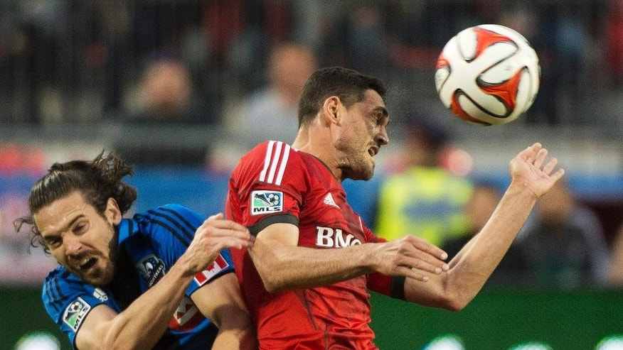 Toronto FC's Gilberto, right, heads the ball past Montreal Impact's Heath Pearce during the first half in the first leg of the Canadian Championship soccer final, in Toronto on Wednesday, May 28, 2014. (AP Photo/The Canadian Press, Nathan Denette)