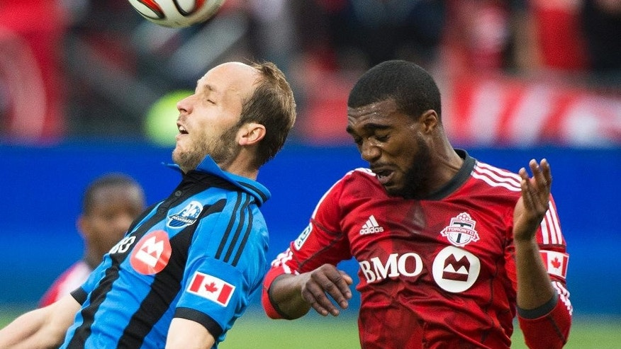 Toronto FC's Ashtone Morgan, right, competes for the ball against Montreal Impact's Justin Mapp during the first half in the first leg of the Canadian Championship soccer final, in Toronto on Wednesday, May 28, 2014. (AP Photo/The Canadian Press, Nathan Denette)