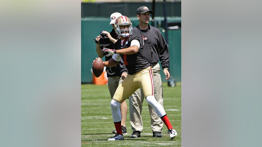 San Francisco 49ers quarterback Colin Kaepernick prepares to throw as coach Jim Harbaugh watches during an NFL football organized team activity, Wednesday, May 28, 2014, in Santa Clara, Calif. (AP Photo/Marcio Jose Sanchez)