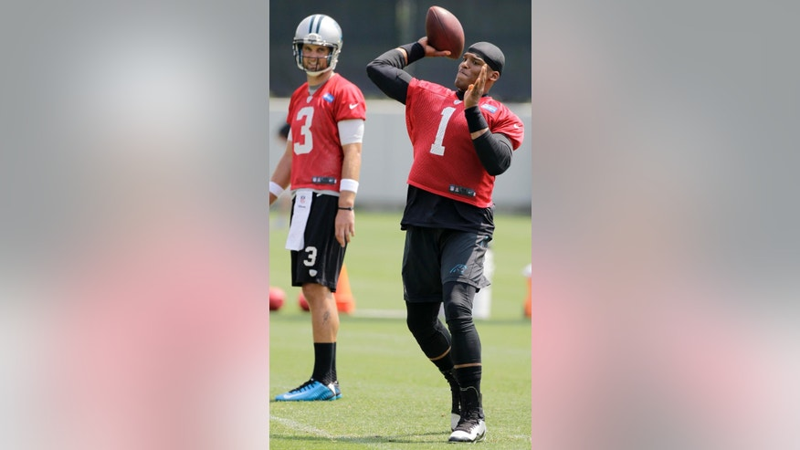 Carolina Panthers' quarterback Cam Newton (1) gets a pass off under the watchful eye of backup quarterback Derek Anderson (3) during an NFL football organized team activity in Charlotte, N.C., Wednesday, May 28, 2014. (AP Photo/Bob Leverone)