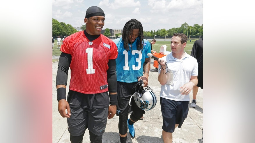 Carolina Panthers' quarterback Cam Newton (1) walks beside rookie receiver Kelvin Benjamin (13), as Benjamin answers a reporters questions following an NFL football organized team activity in Charlotte, N.C., Wednesday, May 28, 2014. (AP Photo/Bob Leverone)