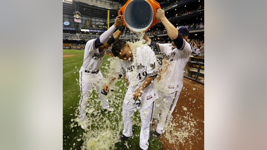 Milwaukee Brewers' Yovani Gallardo is dunked by teammates Mark Reynolds (7) and Carlos Gomez after hitting a game-winning double during the 10th inning of a baseball game against the Baltimore Orioles Tuesday, May 27, 2014, in Milwaukee. The Brewers won 7-6. (AP Photo/Morry Gash)