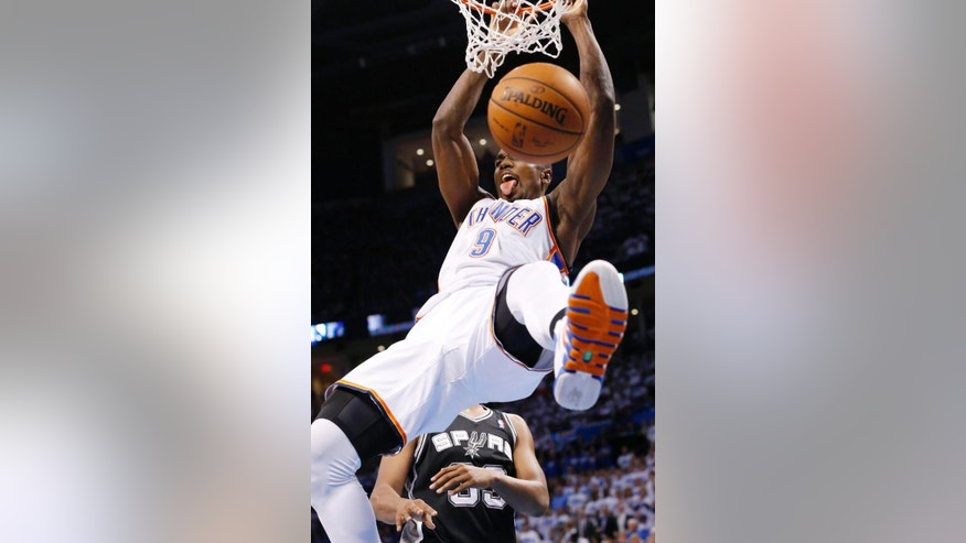 Oklahoma City Thunder forward Serge Ibaka (9) dunks in front of San Antonio Spurs forward Boris Diaw in the second quarter of Game 4 of the Western Conference finals NBA basketball playoff series in Oklahoma City, Tuesday, May 27, 2014. (AP Photo/Sue Ogrocki)