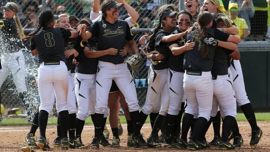 Members of the Oregon NCAA softball team celebrates their 6-2 Super Regional tournament victory over Minnesota in Eugen, Ore., on Sunday, May 25, 2014. The win earned the Ducks a trip to the Women's College World Series in Oklahoma City. (AP Photo/The Register-Guard, Collin Andrew)