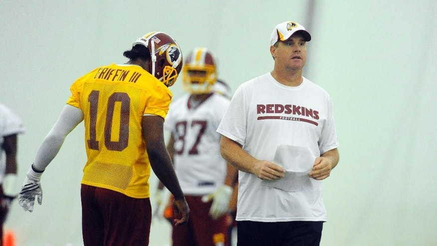 Washington Redskins quarterback Robert Griffin III (10) walks past head coach Jay Gruden during their NFL organized team activity at Redskins training facility, May 29, 2014, in Ashburn, Va. (AP Photo/Richard Lipski)