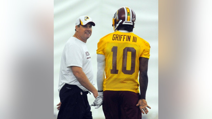 Washington Redskins head coach Jay Gruden talks with quarterback Robert Griffin III  as they pass by each other during an NFL organized team activity at the Redskins training facility Thursday, May 29, 2014, in Ashburn, Va. (AP Photo/Richard Lipski)