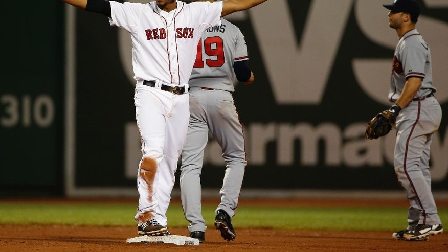 Boston Red Sox's Xander Bogaerts signals safe after Atlanta Braves second baseman Tommy La Stella, right, couldn't handle an infield hit by Dustin Pedroia during the eighth inning of a baseball game at Fenway Park, Thursday, May 29, 2014, in Boston. (AP Photo/Winslow Townson)