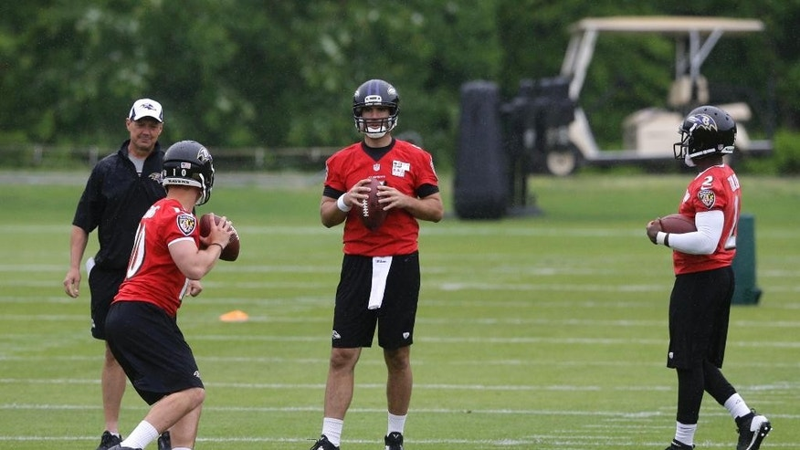 Baltimore Ravens quarterback Joe Flacco, center, watches as fellow quarterbacks Keith Wenning, left, and Tyrod Taylor run drills during an NFL football organized team activity, Thursday, May 29, 2014, at the team's practice facility in Owings Mills, Md. (AP Photo/Patrick Semansky)