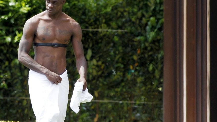 Italy forward Mario Balotelli wears a towel around his waist as he prepares for a sauna during a team training session at Coverciano training grounds, in Florence, Monday, May 26, 2014. In Brazil, Italy is in Group D with England, Uruguay and Costa Rica. (AP Photo/Fabrizio Giovannozzi)