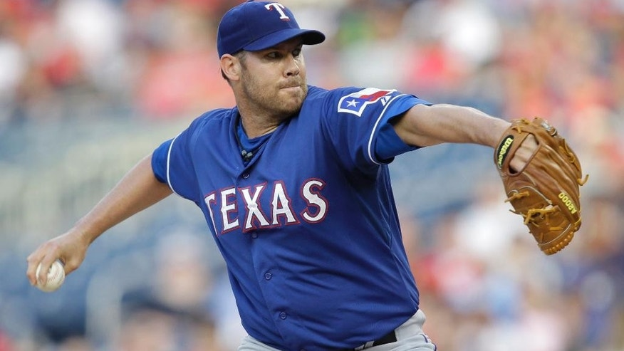 Texas Rangers starting pitcher Colby Lewis delivers the ball to the Washington Nationals during the first inning of a baseball game on Friday, May 30, 2014, in Washington. (AP Photo/Luis M. Alvarez)