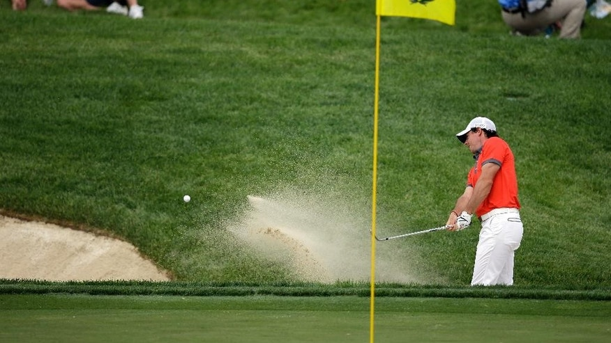 Rory McIlroy, of Northern Ireland, hits from a bunker on the 14th hole during the first round of the Memorial golf tournament Thursday, May 29, 2014, in Dublin, Ohio. (AP Photo/Darron Cummings)
