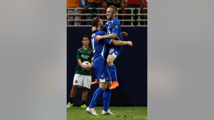 Bosnia's Edin Dzeko, left, is congratulated by teammate Edin Visca after scoring during the first half in an international friendly soccer match against Ivory Coast on Friday, May 30, 2014, in St. Louis. (AP Photo/Jeff Roberson)