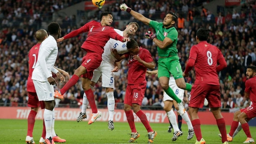England's Gary Cahill, 5, competes for the ball with Peru's Alexander Callens, 4, and goalkeeper Raul Fernandez, 1, during the international friendly soccer match between England and Peru at Wembley Stadium in London, Friday, May 30, 2014.  (AP Photo/Matt Dunham)
