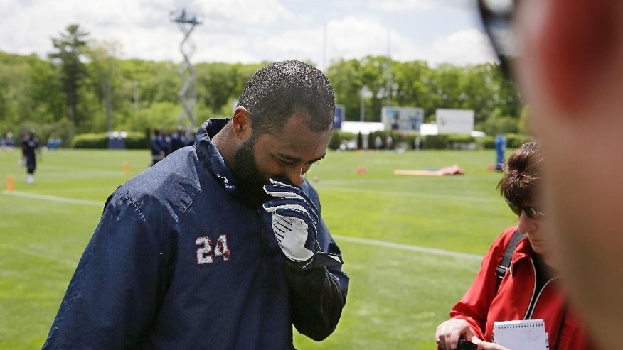 New England Patriots corner back Darrelle Revis (24) walks up to a media availability on the field at the conclusion of an organized team activity at the NFL football team's facility Friday, May 30, 2014 in Foxborough, Mass. (AP Photo/Stephan Savoia)