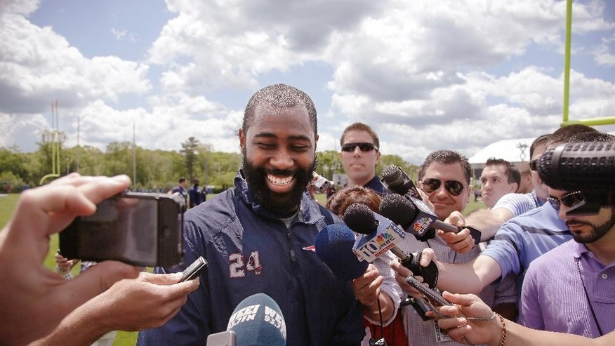 New England Patriots corner back Darrelle Revis (24) talks with members of the media at the conclusion of an  organized team activity at the NFL football team's facility Friday, May 30, 2014 in Foxborough, Mass. (AP Photo/Stephan Savoia)