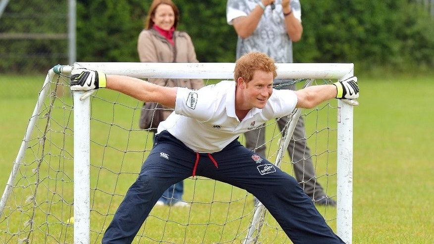 Britain's Prince Harry prepares to stop a penalty, during a short soccer kick about at the Inspire Suffolk centre for young people in Ipswich, eastern England, Thursday May 29, 2014. The prince began his day at the youth organisation which uses education and sport to improve young people's lives. (AP Photo/John Stillwell, Pool)
