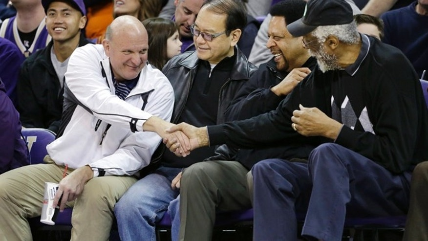 "Jan. 25, 2014: Then-Microsoft CEO Steve Ballmer, left, shakes hands with former NBA players Bill Russell, right, and ""Downtown"" Freddie Brown as Omar Lee looks on during an NCAA college basketball game between Washington and Oregon State in Seattle."