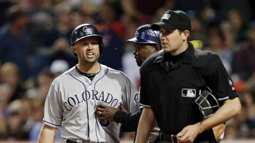 Colorado Rockies' Michael Cuddyer, left, barks at home plate umpire John Tumpane after being called out on strikes in the sixth inning of a baseball game against the Cleveland Indians on Friday, May 30, 2014, in Cleveland. (AP Photo/Mark Duncan)