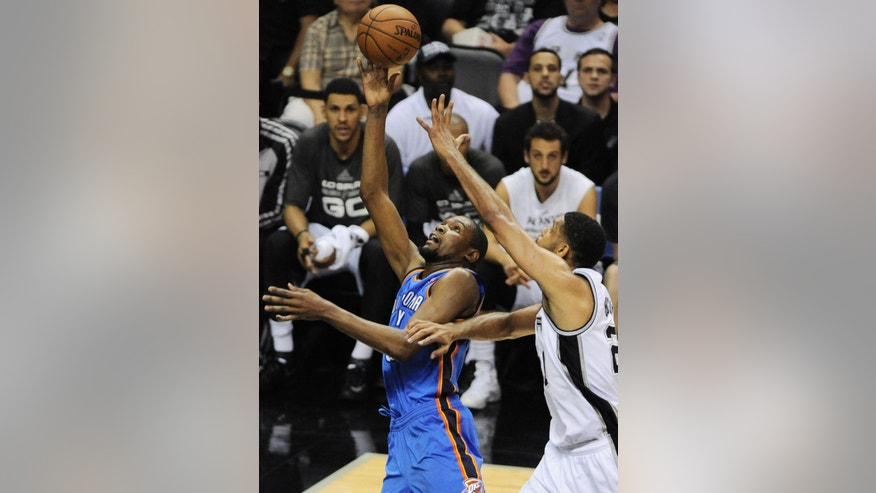 Oklahoma City Thunder forward Kevin Durant, left, shoots against San Antonio Spurs forward Tim Duncan during the second half of Game 5 of the NBA basketball Western Conference finals, Thursday, May 29, 2014, in San Antonio. San Antonio won 117-89. (AP Photo/Darren Abate)