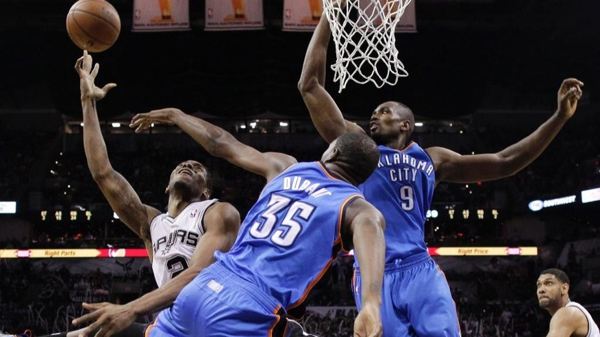 San Antonio Spurs' Kawhi Leonard (2) shoots over Oklahoma City Thunder's Kevin Durant (35) and Serge Ibaka (9) during the second half of Game 5 of the Western Conference finals NBA basketball playoff series, Thursday, May 29, 2014, in San Antonio. San Antonio won 117-89. (AP Photo/Eric Gay)