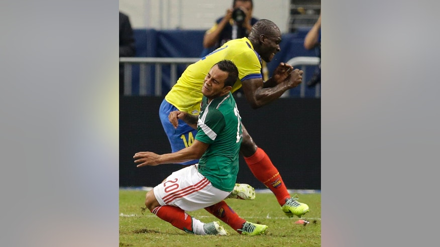 Mexico's Luis Montes collides with Ecuador's Segundo Castillo, rear, as the two were competing for the ball during the first half of a friendly soccer match, Saturday, May 31, 2014, in Arlington, Texas. Montes left the game on a stretcher with an unknown leg injury. (AP Photo/Tony Gutierrez)