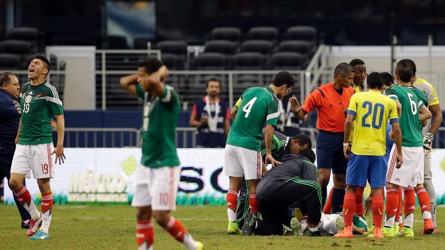 Mexico's Oribe Peralta (19) yells as medical staff attend to injured teammate Luis Montes, on ground, after Montes suffered an unknown leg injury during a collision with Ecuador's Segundo Castillo in the first half of a friendly soccer match, Saturday, May 31, 2014, in Arlington, Texas.  (AP Photo/tony gutierrez)