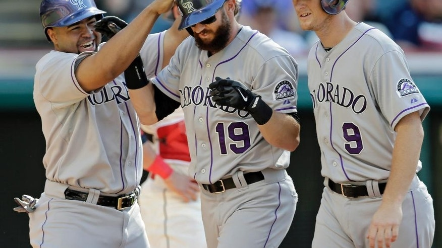 Colorado Rockies' Charlie Blackmon (19) is congratulated by Wilin Rosario, left, and DJ LeMahieu (9) after Blackmon's three-run home run off Cleveland Indians relief pitcher Josh Outman in the seventh inning of a baseball game Saturday, May 31, 2014, in Cleveland. (AP Photo/Mark Duncan)