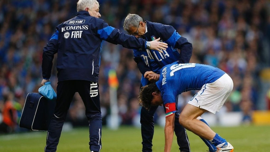 Italy's Riccardo Montolivo, lower right, limps off the pitch after getting injured from a tackle during their international friendly soccer match at Craven Cottage, London, Saturday, May 31, 2014. (AP Photo/Sang Tan)
