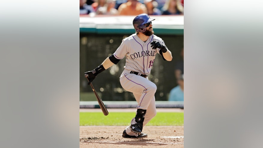 Colorado Rockies' Charlie Blackmon singles to drive in a run in the third inning of a baseball game against the Cleveland Indians Saturday, May 31, 2014, in Cleveland. (AP Photo/Mark Duncan)
