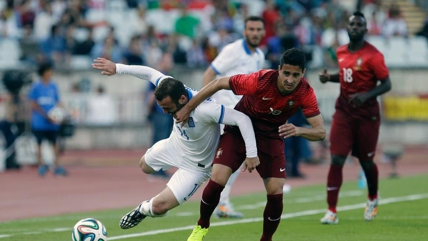 Greece's Dimitris Salpingidis, left, tussles for the ball with Portugal's Andre Almeida during a friendly soccer match between Portugal and Greece at the National stadium, in Oeiras, near Lisbon, Saturday, May 31, 2014. The game is a warm-up match for both teams ahead the World Cup in Brazil. (AP Photo/Francisco Seco)