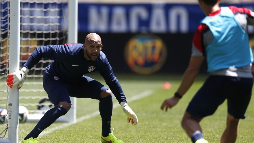 United States goalkeeper Tim Howard, left, defends against teammate Brad Davis during a scrimmage at the team's open workout, Saturday, May 31, 2014, in Harrison, N.J. The United States are scheduled to Turkey in an international friendly soccer game on Sunday. (AP Photo/Julio Cortez)