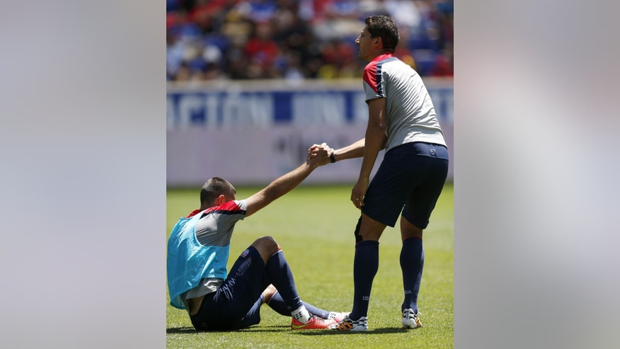 United States' Clint Dempsey, bottom, is helped up by teammate Omar Gonzalez after a play in which Dempsey fell down and grabbed his ankle during an open practice, Saturday, May 31, 2014, in Harrison, N.J. The United States will face Turkey in an international friendly on June 1. (AP Photo/Julio Cortez)