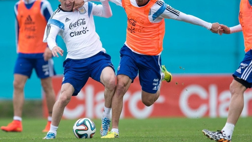 Argentina's national soccer player Lionel Messi, left, fights for the ball with player Enzo Perez during a training session in Buenos Aires, Argentina, Saturday, May 31, 2014. Argentina is training for the Brazil 2014 World Cup.(AP Photo/Natacha Pisarenko)
