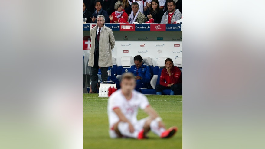 Swiss head coach Ottmar Hitzfeld, watches, while Switzerland's Xherdan Shaqiri sits on the ground during the international friendly soccer match between Switzerland and Jamaica at the Swissporarena in Lucerne, Switzerland, Friday, May 30, 2014. Switzerland are preparing for the upcoming FIFA soccer World Cup in Brazil starting on 12 June. (AP Photo/Keystone, Peter Klaunzer)