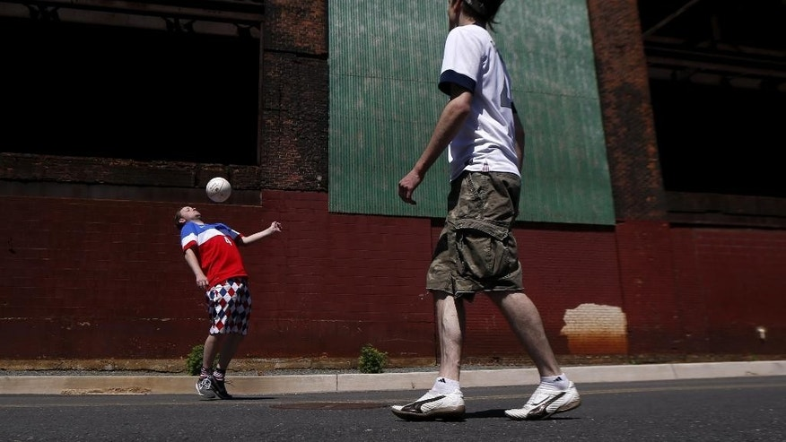 Jason Burke, 35, left, and Simon Collum, 35, both from Ridgewood, N.J., play soccer near a warehouse adjacent to Red Bull Arena before the start of an international soccer friendly between Turkey and the United States, Sunday, June 1, 2014, in Harrison, N.J. (AP Photo/Julio Cortez)