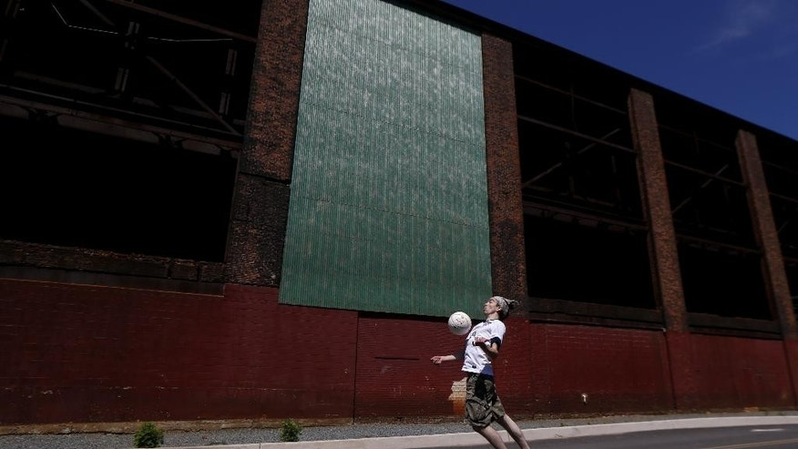 Simon Collum, 35, of Ridgewood, N.J., plays soccer near a warehouse adjacent to Red Bull Arena before the start of an international soccer friendly between Turkey and the United States, Sunday, June 1, 2014, in Harrison, N.J. (AP Photo/Julio Cortez)