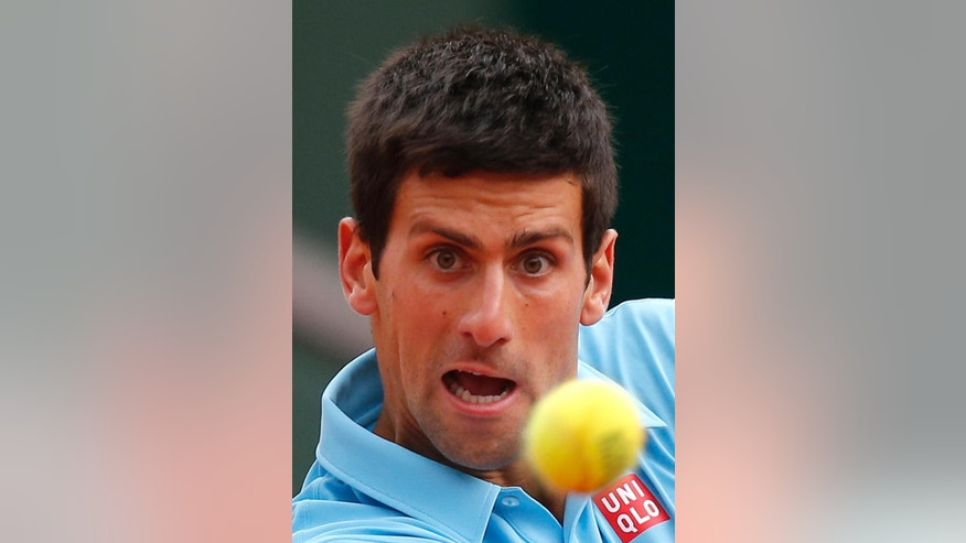 Serbia's Novak Djokovic eyes the ball as he plays France's Jo-Wilfried Tsonga during their fourth round match of  the French Open tennis tournament at the Roland Garros stadium, in Paris, France, Sunday, June 1, 2014. (AP Photo/David Vincent)