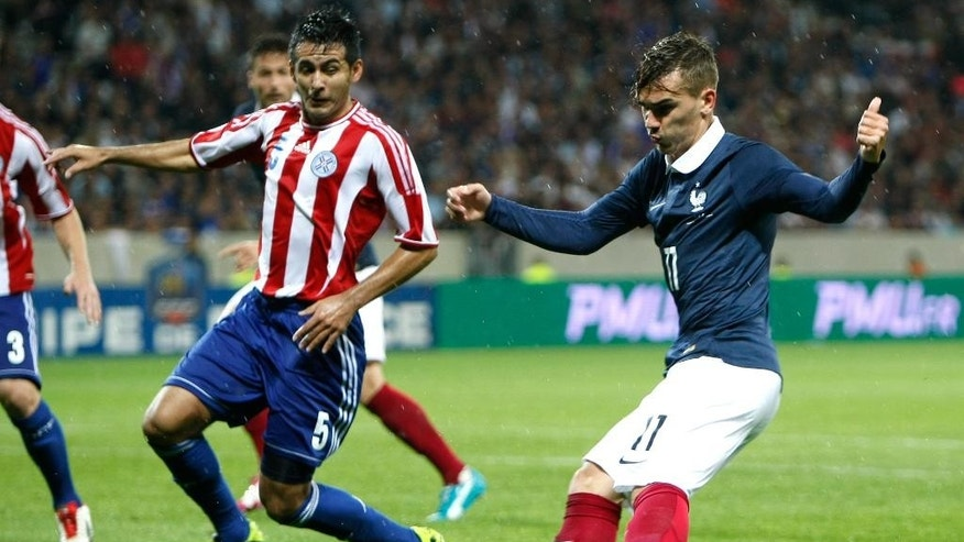 French soccer team forward Antoine Griezmann, right, challenges for the ball with Paraguayan soccer team defender Luis Carlos Cardozo Espillaga, during the friendly soccer match between France and Paraguay at the Allianz Riviera Stadium, in Nice, southeastern France, Sunday, June 1, 2014. France is preparing for the upcoming soccer World Cup in Brazil starting on 12 June. (AP Photo/Claude Paris)