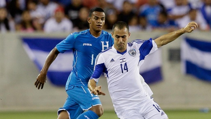 Israel's  Neftali Vermouth Gil (14) dribbles around Honduras' Rony Martinez (16) in the first half during a soccer match Sunday, June 1, 2014, in Houston. (AP Photo/Bob Levey)
