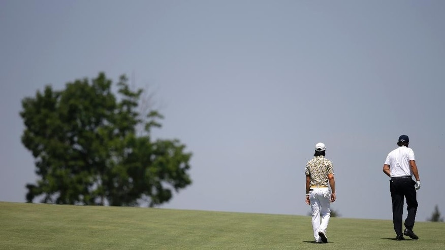 Ryo Ishikawa, left, of Japan, and Phil Mickelson, right, walk down the 10th fairway during the final round of the Memorial golf tournament on Sunday, June 1, 2014, in Dublin, Ohio. (AP Photo/Darron Cummings)