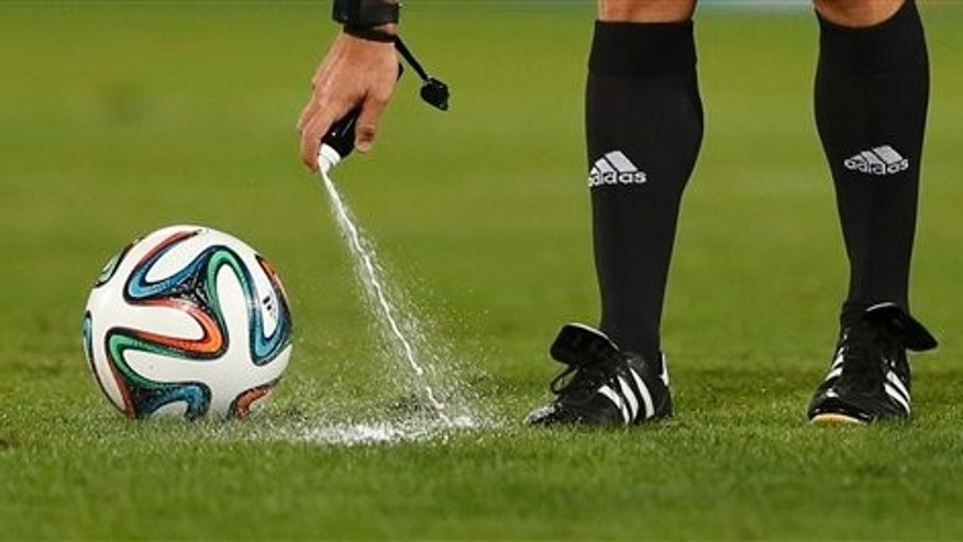 FILE - In this Wednesday, Dec. 18, 2013, file photo, referee Carlos Velasco of Spain marks a line with vanishing spray during the semi final soccer match between Raja Casablanca and Atletico Mineiro at the Club World Cup soccer tournament in Marrakech, Morocco. For the first time at a World Cup, technology will be used to determine whether a ball crosses the goal line during matches at the upcoming tournament in Brazil. With vanishing spray also being used to prevent encroachment by defenders making up a wall during free kicks, officials at the highest level of the worlds most popular sport are finally getting some assistance. (AP Photo/Matthias Schrader, File)